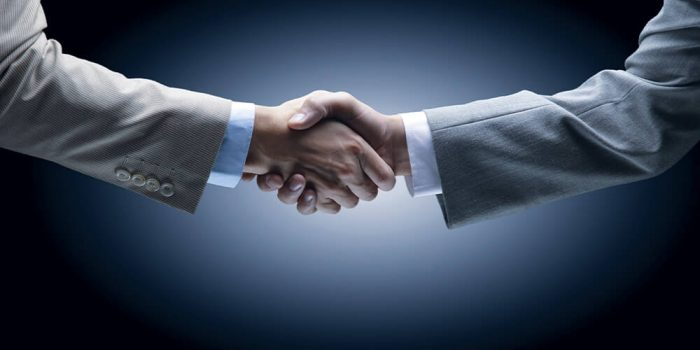 Two per head bookie agents shaking hands over layoff account concept